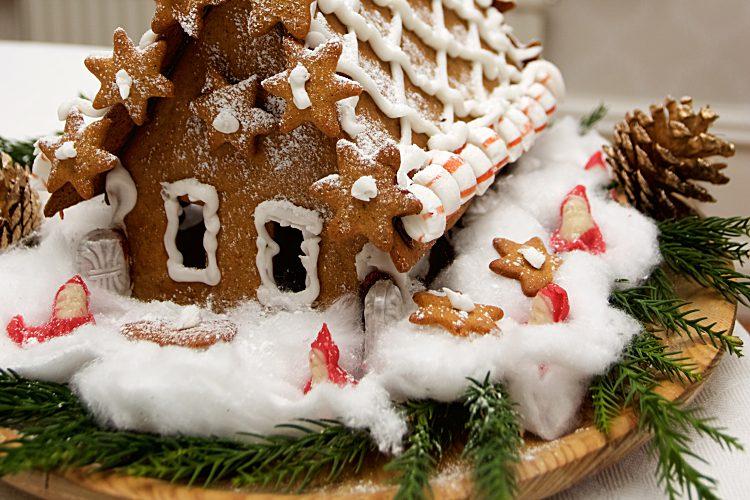Pepparkakor och pepparkakshus med nejlikor, ingefära, kanel, pomeransskal och smör