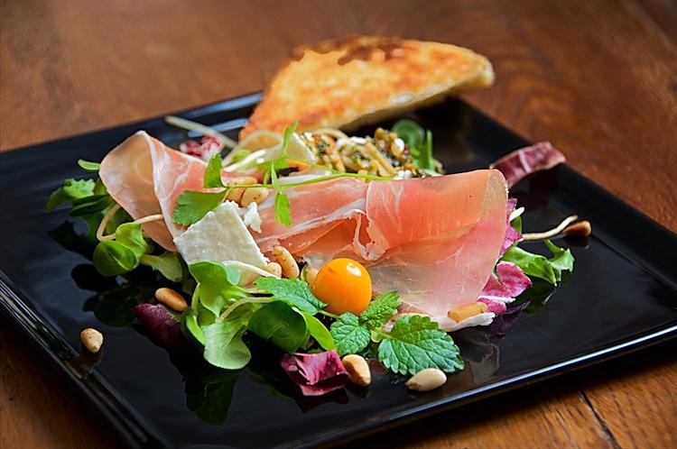 Parmaskinka, fårost, pesto och pinjenötter på salladsbädd